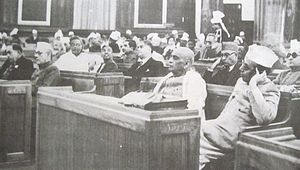Large group of men sitting on benches in a room