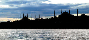 Silhouette of several buildings with domes and spires in front of an open waterway at twilight