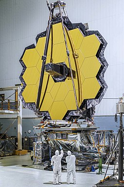 The primary mirror assembly of James Webb Space Telescope under construction. This is a segmented mirror and its coated with Gold to reflect (orange-red) visible light, through near-infrared to the mid-infrared JWST Full Mirror.jpg