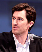 Joseph Kosinski in front of a microphone during a press conference.
