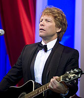 Jon Bon Jovi, a caucasian male in his mid-40s with dark blond hair, wears a black suit and white shirt with a black bow-tie. He is seen with a black acoustic guitar strapped across his stomach.