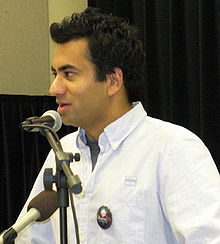 A man giving a speech. He wears a white blouse with a dark label pin; in front of him, there are two microphones.