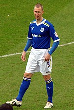 A man with a shaven head wearing a blue football jersey, white shorts and blue socks. He is standing on a grass pitch