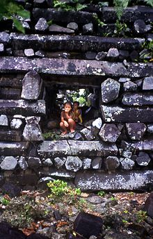 Image of two children crouching in a square passage through a wall constructed of dark grey columnar basalt pieces.