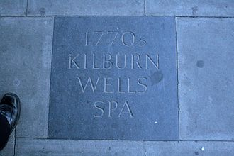 Kilburn, London - A paving stone commemorates the former Wells on the corner of Belsize Road and the High Road