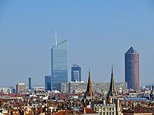 Quatre gratte-ciels émergent du panorama lyonnais, dont un en forme de crayon.