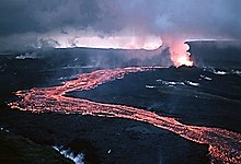 A red-hot lava flow streams out of a fuming vent, meandering past the viewer under a low cloudy sky.