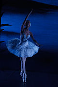 A ballerina in a white tutu, posing en point on a dimly lit stage