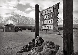 "Manzanar - ""Wooden sign at entrance to the Manzanar War Relocation Center with a car at the gatehouse in the background."", c. 1943"