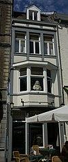 foto van Huis met lijstgevel, met gekoppelde vensters in Naamse steen en verticale reliefbanden.