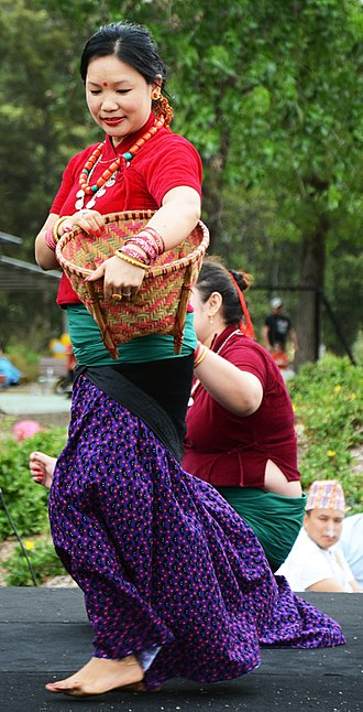 Magars - A Magar woman dancing in her traditional dress carrying a bamboo basket during the festival of Maghe Sakranti in Sydney.