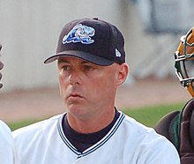 A man wearing a white baseball jersey and navy-blue baseball cap pictured from the shoulders up