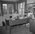 Mevrouw Svendsen bestudeert een bot zittend aan een bureau waarop boeken en bott, Bestanddeelnr 252-8749.jpg