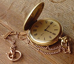 A gold pocket watch with hunter case and watch chain