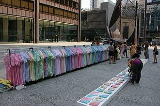 Maternal mortality in the United States - Image of 1,200 hospital gowns hung from a rack in the middle of Daley Plaza in Chicago to represent all the mothers who died during childbirth in the USA in 2013. Some of the gowns are folded into triangles to mimic the way the American flag is folded at the funeral of a soldier. The gowns are pink, blue, yellow, green, and purple with various patterns.