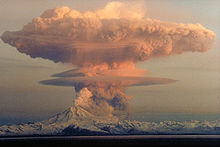 A large ash cloud rising into the air from an erupting volcano