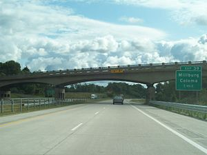 Interstate Highway standards - I-94 in Michigan, showing examples of non-interchange overpass signage in median, upcoming exit signage on right shoulder, a 1950s overpass with height restriction signage, newly installed cable median barrier, and parallel grooved pavement with shoulder rumble strips