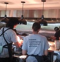 Dwie kelnerki i jeden kucharz odwracają twarz od kamery, miski na blacie ze stali nierdzewnej, trzy wiszące lampy zwisają z sufitu