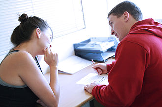 Personal trainer - Personal trainer assessing a client's goals and needs as they write a fitness program