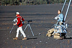 Pete Conrad (left) carries the gnomon while Al Bean carries the Hand Tool Carrier during geology training at the Cinder Lake crater field.jpg