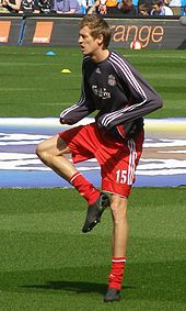 A man in a football uniform, standing on one leg, warming up before a football match