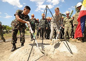Balikatan - Philippine army Lt. Col. Henry Bellan, left, and U.S. Army Lt. Col. John Garrity bury a time capsule during the construction of a footbridge in San Narciso, Zambales, Balikatan 2013