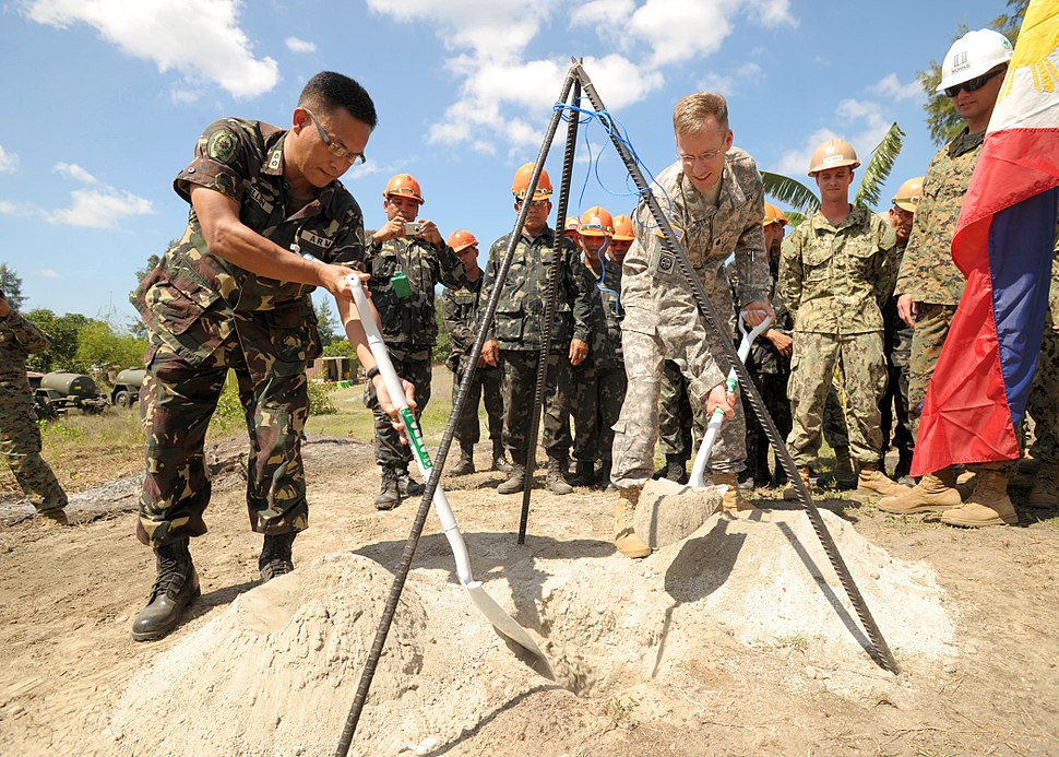 Philippine army Lt. Col. Henry Bellan, left, and U.S. Army Lt. Col. John Garrity, the deputy commanders of Joint Civil Military Operations Task Force, bury a time capsule containing the construction plans for 130318-N-VN372-145