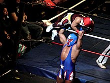 Color photo of a masked wrestler lifting a smaller masked wrestler over his head.