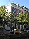 Hoekpand Kloksteeg met omlopend schilddak en eenvoudige gevel van drie vensterassen onder rijk gesneden Lod. XIV-lijst. In de Kloksteeg tuinmuur met poortje en gevelsteen
