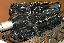 A front right view of a black-painted aero engine, the words 'Rolls-Royce' appear in red. The engine has yellow electrical wiring and is sitting on a wooden pallet.