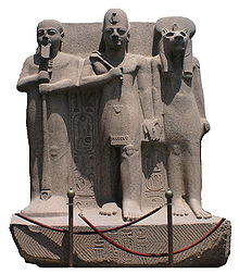 Statue of a man with a crown standing between a man holding a staff and a woman with the head of a lioness