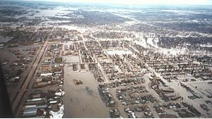 An overhead view of neighborhoods surrounded by water. The flooding can be seen for several miles.
