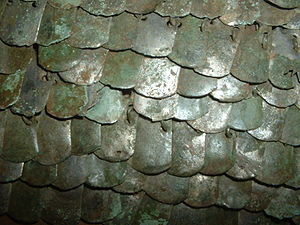 "Scale armour - Fragment of Lorica squamata. Each plate has six holes and the scales are linked in rows. Only the ""lower most"" holes are visible on most scales, while a few show the pair above and the ring fastener passing through them."
