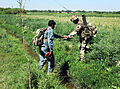 Royal Scots Dragoon Guards Soldier Helps Afghan National Policeman Across a Ditch in Afghanistan MOD 45153317.jpg