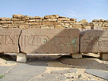 Enormous beam of granite with large hieroglyphs on it, some of which are still green