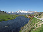 A midsized river flowing through grassland with snow-capped mountains in the background