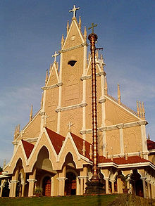 Tall, tan-colored Christian church with red, pointed roofs