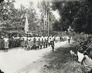 Tupua Tamasese Lealofi III - Mau carrying the coffin of Tupua Tamasese Lealofi III. Standing to the right wearing a single white stripe on his lava-lava, the Mau uniform, is Mata'afa Faumuina Fiame Mulinu'u I, who later became the President of the Mau.