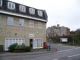 Stone 3 storey building with white frames windows on street junction. Sign saying shop.