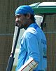 A Sri Lankan cricketer wearing a blue shirt and a blue cloth of his head. He also has a guard on his hand.