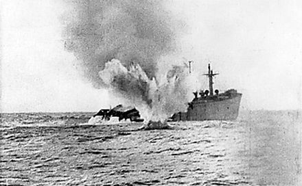 A U-boat shells a merchant ship which has remained afloat after being torpedoed. Torpedoed merchant ship.jpg