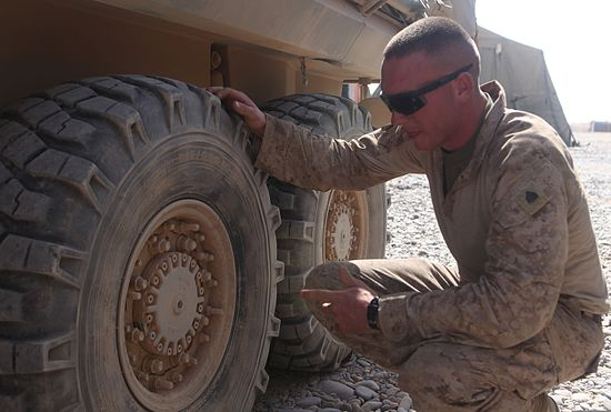U.S. Marine Corps Sgt. Thomas Marshall, a light armored vehicle mechanic with the 2nd Light Armored Reconnaissance Battalion, 2nd Marine Division (Forward), checks the tire pressure on a vehicle at Forward 110701-M-VI276-002.jpg