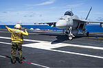 U.S. Navy Aviation Boatswain's Mate (Handling) Jose Ramos directs an F-A-18E Super Hornet aircraft assigned to Strike Fighter Squadron (VFA) 27 on the flight deck of the aircraft carrier USS George Washington 130821-N-TE278-082.jpg