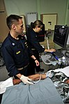 U.S. Navy Lt. Tyler Vachon, left, and Cmdr. Danielle Taysom look at the ultrasound of a mass on the right arm of an Indonesian man in the radiology room aboard Military Sealift Command hospital ship USNS Mercy 120602-O-ZZ999-014.jpg