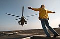 US Navy 040428-N-9849W-001 Steve Philfer, from San Diego, Calif., a civilian mariner assigned to the Military Sealift Command, gives the pilots of a SH-3 Sea King the signal to lift from the flight deck.jpg