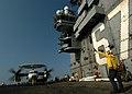 US Navy 050217-N-8704K-003 Aviation Boatswain Mate 3rd Class Zolli Goodman directs the movement of an E-2C Hawkeye.jpg