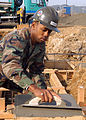 US Navy 050321-N-2385R-005 Engineering Aide Constructionman Doug Gaffney, assigned to Naval Mobile Construction Battalion Four Zero (NMCB-40), Detachment Sasebo, uses a magnesium float to even out concrete.jpg