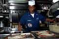 US Navy 070217-N-3038W-135 Operations Specialist 2nd Class Tracey Nkrumah puts toppings on a pizza on the forward mess decks in preparation for lunch and dinner aboard the Nimitz-class aircraft carrier USS John C. Stennis (CVN.jpg