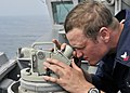 US Navy 090505-N-2638R-002 Boatswain's Mate 2nd Class Jeff Stillman, from Pocahontas, Ill, uses an alidade telescope to look for surface contacts from the bridge wing of guided-missile destroyer USS Mustin (DDG 89).jpg