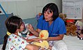 US Navy 090706-F-7885G-043 Monica Castaneda, a child life specialist with Operation Smile, introduces a young patient to a stethoscope and breathing mask.jpg